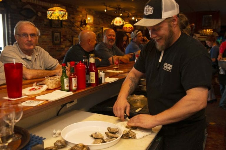awful arthur's shucking oysters at the bar